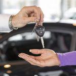 Salesman handing over car keys in dealership